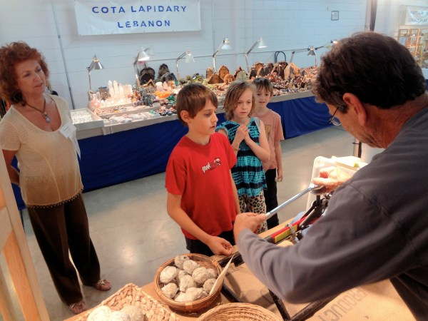 Portland Regional Gem and Mineral Show Vendor breaks a geode as children look on in awe